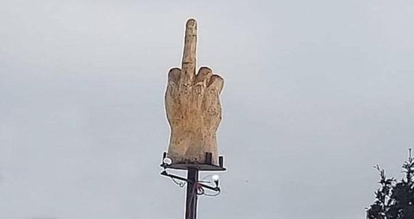 Тэд Пелкей установил статую огромного «нецензурного жеста» , направленную на свой город с местными властями. На монумент было потрачено 4000 USD из семейного бюджета.Причиной , побудившей его